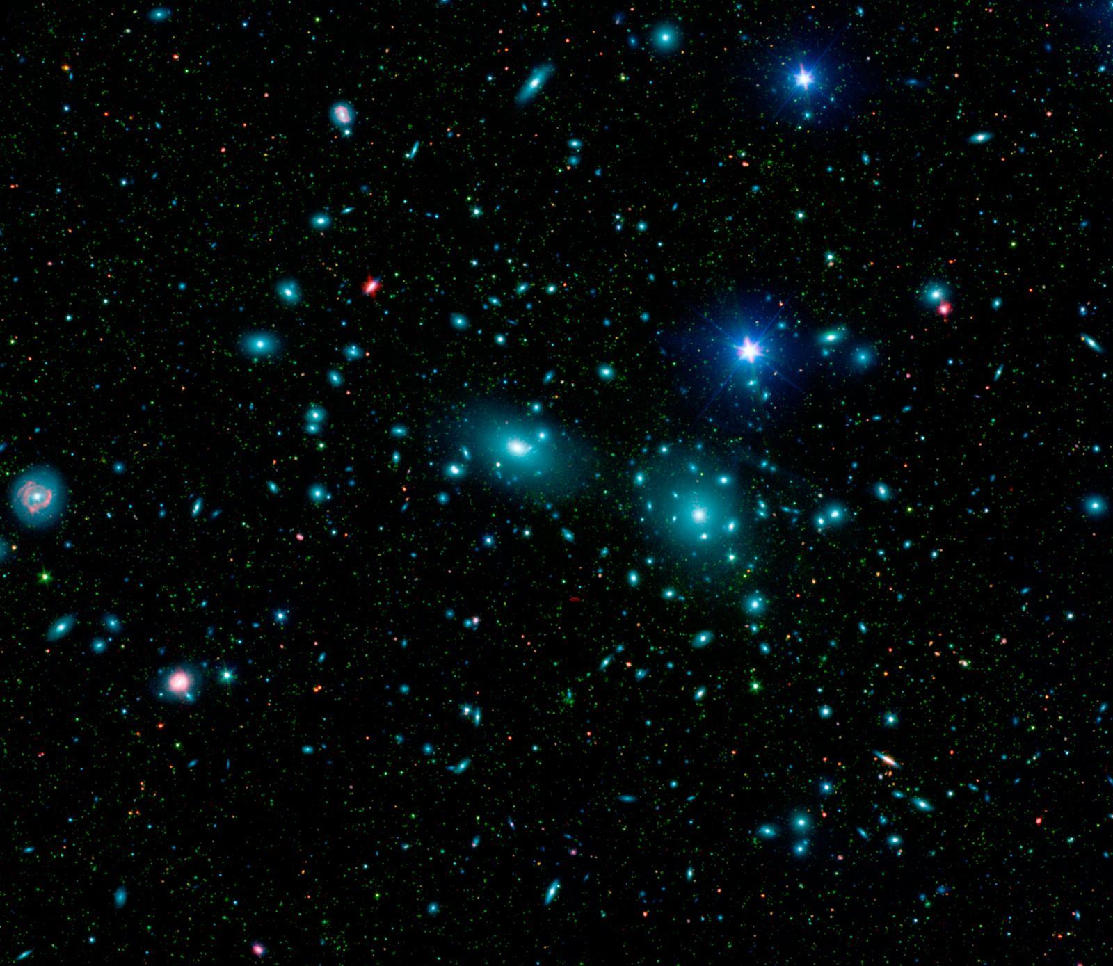 Toen Fritz Zwicky het Coma-cluster onderzocht, ontdekte hij dat er iets vreemds aan de hand was. Volgens zijn berekeningen op basis van de snelheden van de sterrenstelsels, moest de massa van dit cluster zo'n 400 keer groter zijn dan hij uit het licht van sterrenstelsels en gas kon afleiden. (Bron: NASA / JPL-Caltech / L. Jenkins (GSFC))